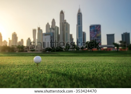 Playing golf at sunset. Golf ball is on the tee for a golf ball on the green grass of the golf course against the background the city skyscrapers at sunset - stock photo