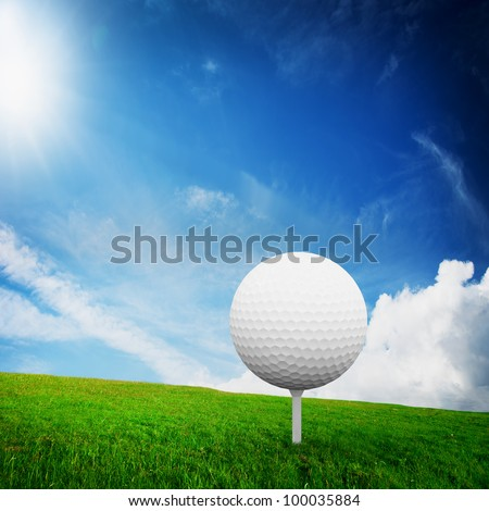 Playing golf. Ball on tee, on green golf field. Sunny summer scene
