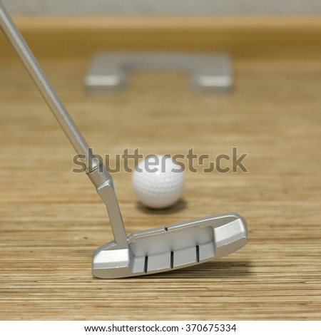 Playing golf in the house or office. Golf clubs, balls and hole. Mini golf. - stock photo