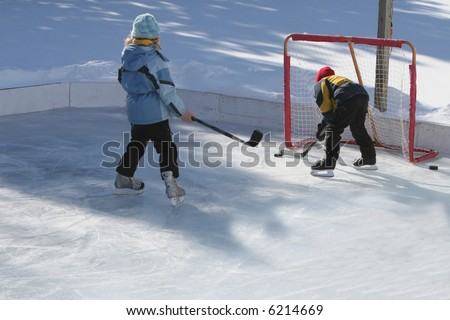 Playing ice hockey on an outdoor ice rink - stock photo