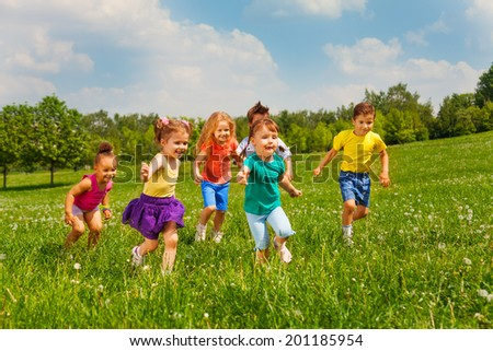 Playing kids in green field during summer - stock photo