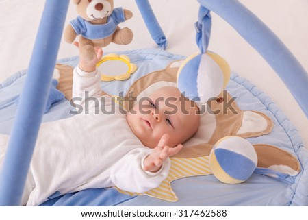 playing little newborn baby with toys - stock photo