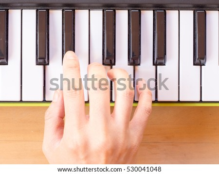Playing mini digital piano, Dm,  on wooden table