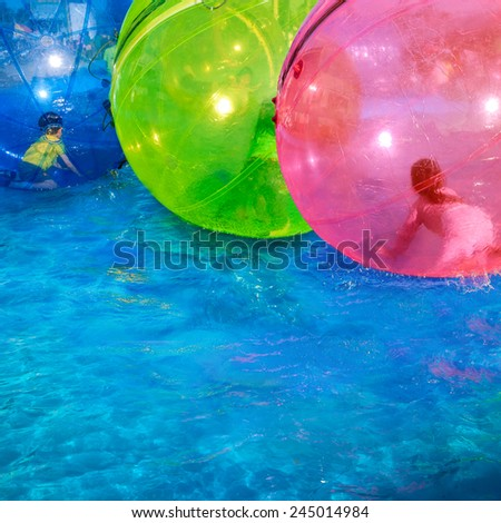 Playing of child in water walking balls on open swimming pool.