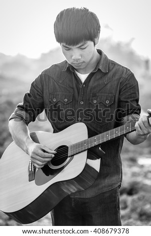 Playing on acoustic guitar outdoor, Black and white photo - stock photo
