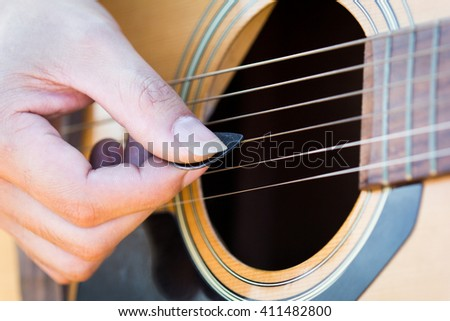 Playing on acoustic guitar outdoor,Black and white photo - stock photo