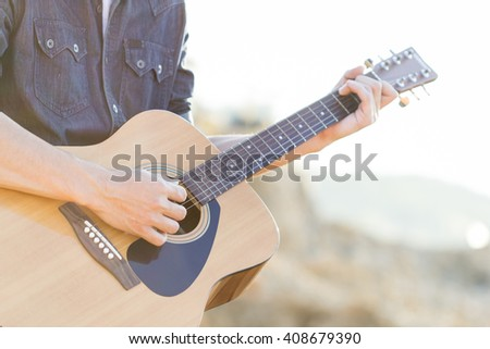 Playing on acoustic guitar outdoor, vintage - stock photo