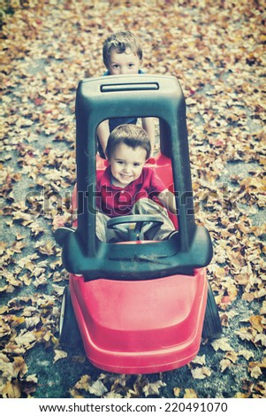 Playing outside, a young happy boy pushes his younger brother who is smiling with joy in a toy car on a driveway covered in fall leaves during the fall season.  Filtered for a retro, vintage look.  - stock photo