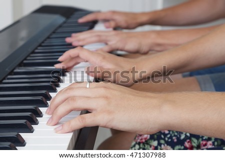 Playing piano four hands, close-up