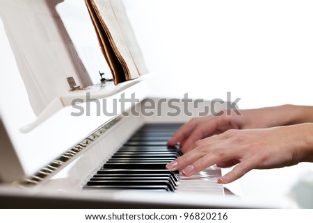Playing Piano (shallow DOF; color toned image) - stock photo