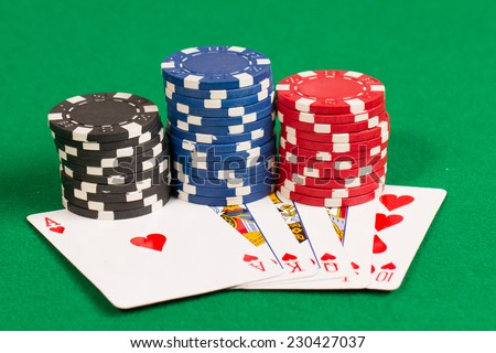 Playing Poker Chips and a royal flush cards in green background