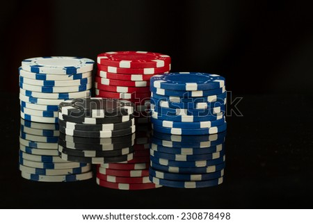 Playing Poker Chips in reflective black background - stock photo