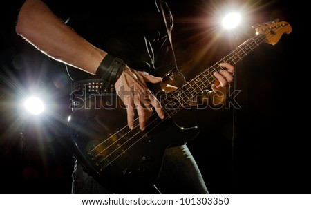 playing rock guitarist surrounded with lights - stock photo