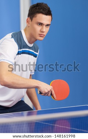 Playing table tennis. Confident young men holding a table tennis racket and looking away - stock photo