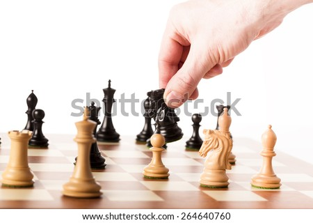 Playing the chess game - a hand moving the black knight - making strategic decisions - stock photo
