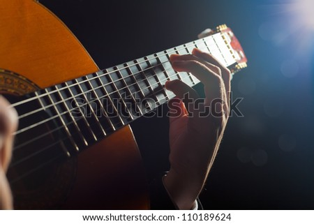 Playing the guitar. Musical instrument with performer hands - stock photo