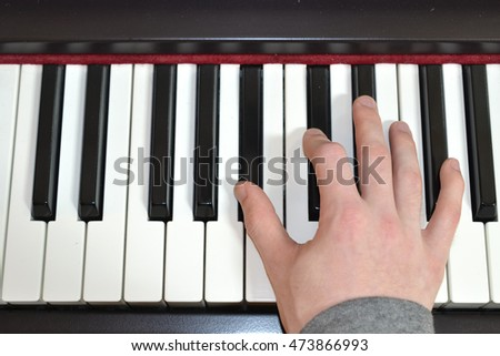 Playing the piano keyboard close up. Electronic piano instrument with isolated hand. Learning to play music. Beautiful music performance and playing chords. Songs, harmony, and artistic background