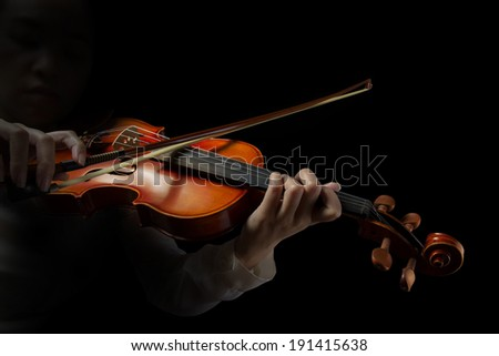 Playing the violin. Musical instrument with hands on dark background. - stock photo