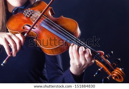Playing the violin. Musical instrument with performer hands on dark background. - stock photo