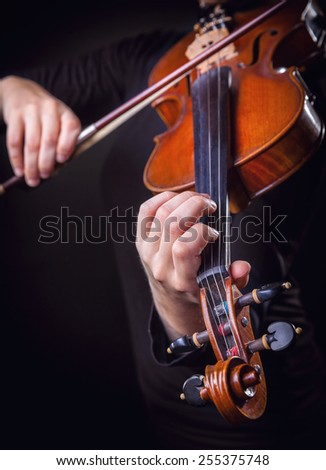 Playing the violin. Musical instrument with performer hands on dark background. Focus on the hand - stock photo