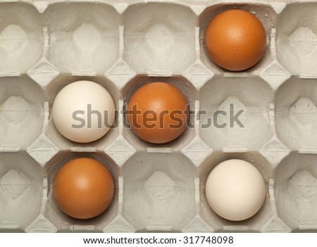 Playing tit tat toe game with eggs in a tray - stock photo