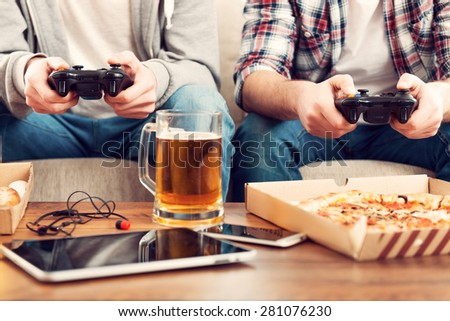 Playing video games. Close-up of two men playing video games while sitting on sofa - stock photo