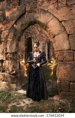playing with fire of a young lady with Gothic Dagger - stock photo