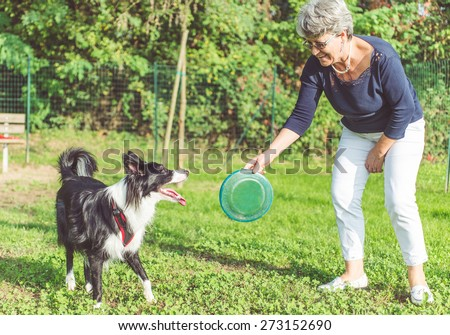 playing with the dog. middle age woman playing with her border collie dog in the park. throwing frisbee - stock photo