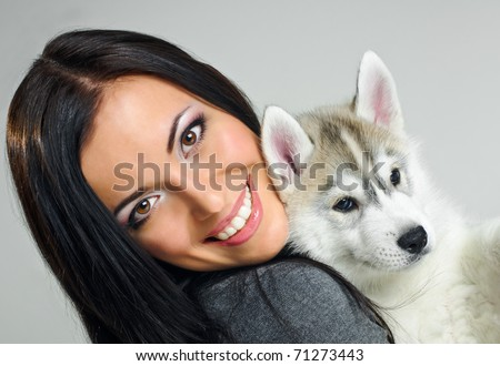 playing woman with puppy of siberian haski on gray background