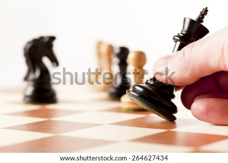 Playing wooden chess pieces - moving the black king - stock photo