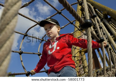 Playing young boy in rope bridge, in red pullover