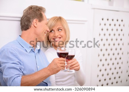 Pleasant affinity. Cheerful delighted adult couple holding glasses and drinking wine while bonding to each other - stock photo