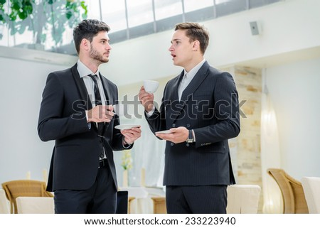 Pleasant business conversation. Two successful businessman standing in the restaurant and drink coffee while talking to each other. Businessman dressed in formal wear. - stock photo