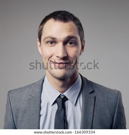 Pleasant businessman portrait on grey background - stock photo