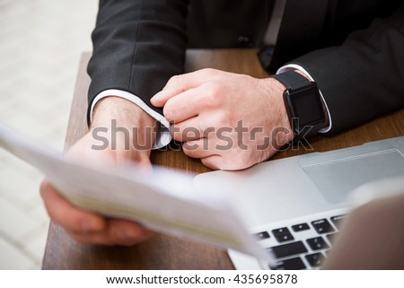 Pleasant businessman sitting at the table