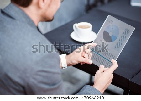 Pleasant businessman using tablet