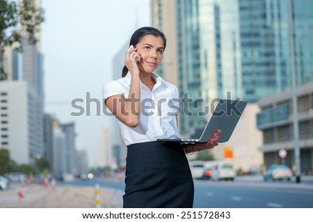 Pleasant conversation. Smiling businesswoman standing on a street in formal attire holding a laptop while talking on cell phone. Arab businessman working on laptop in among the skyscrapers in Dubai