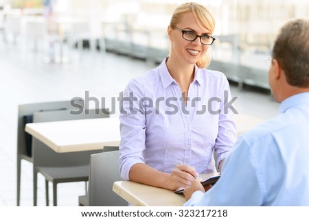 Pleasant meeting. Cheerful delighted charming businesswoman sitting at the table with her colleague and making notes while discussing business matters - stock photo