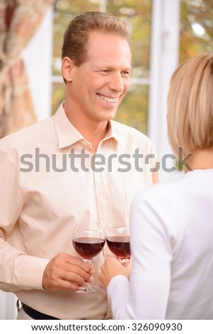 Pleasant moment. Overjoyed handsome smiling man looking at her wife and holding glass while drinking wine together - stock photo