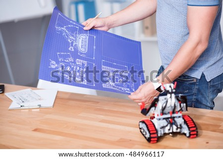 Pleasant professional engineer holding a scheme
