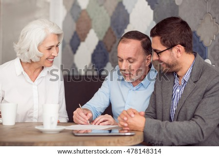 Pleasant senior man signing papers