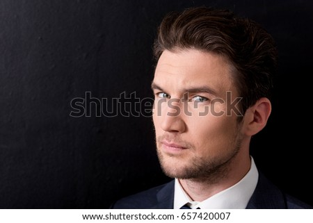 Pleasant serious businessman is standing against dark wall