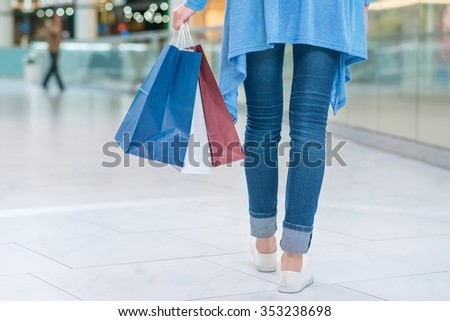 Pleasant shopping. Active young woman holding packages and walking along shopping mall.