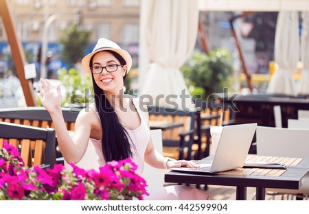 Pleasant smiling woman sitting at the table