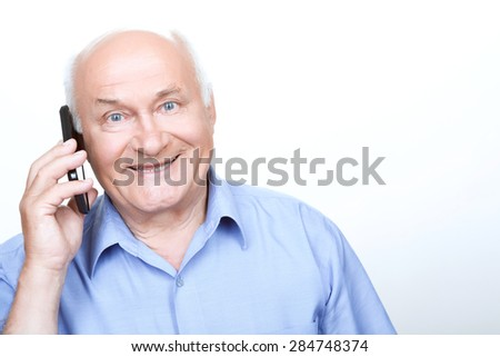 Pleasant talk. Agreeable grandfather holding the mobile phone and smiling while talking - stock photo