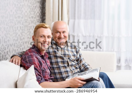 Pleasant time. Attractive young grandson together  with his grandpa and holding album - stock photo