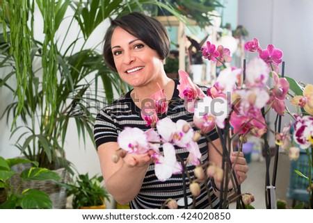 Pleasant  woman florist showing a multicolored phalaenopsis flowers in the floral shop - stock photo