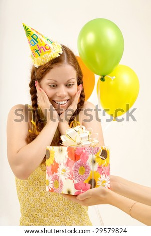 Pleasantly surprised birthday woman accepts a gift - stock photo