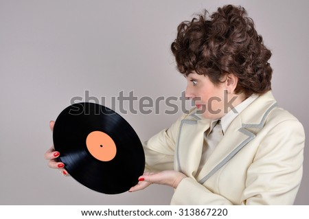 Pleasantly surprised woman holding and looking at a vinyl record. Vintage style photo