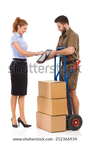Please confirm a delivery. Smiling office female worker receives delivery from messenger and tapping at digital tablet. Full length studio shot isolated on white. - stock photo